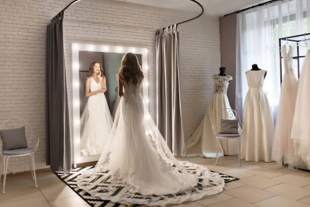 a bride to be tries out wedding dresses