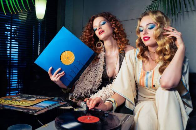 two girls in 70's fashion pieces listening to record player