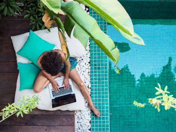 A nomad worker uses laptop by a pool
